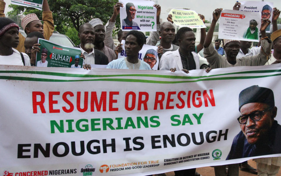 Protesters carry placards to demand that ailing President Mohammadu Buhari resume work or resign in Abuja, on August 7, 2017.   Dozens of protesters in collaboration with civil society marched through the streets to demand that Nigerian President Muhammadu Buhari who has been away on medical vacation in London for more than three months resume work or resign his job.  / AFP PHOTO / PHILIP OJISUA